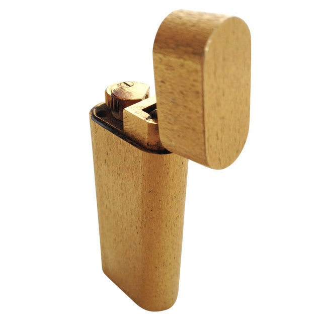 18-karat gold plated Cartier lighter featuring a oval body with beautiful finely brushed finish. Engraved along the front...
