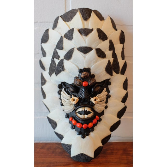 A Brazilian Amazon tribal face mask made from fish bone, fish scales, wood, berries, and piranha teeth. The back of the...