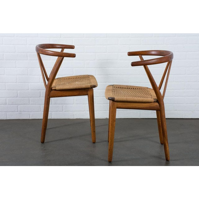 This pair of Mid-Century Modern chairs were designed by Henning Kjærnulf for Bruno Hansen, Denmark, circa 1960's. They...