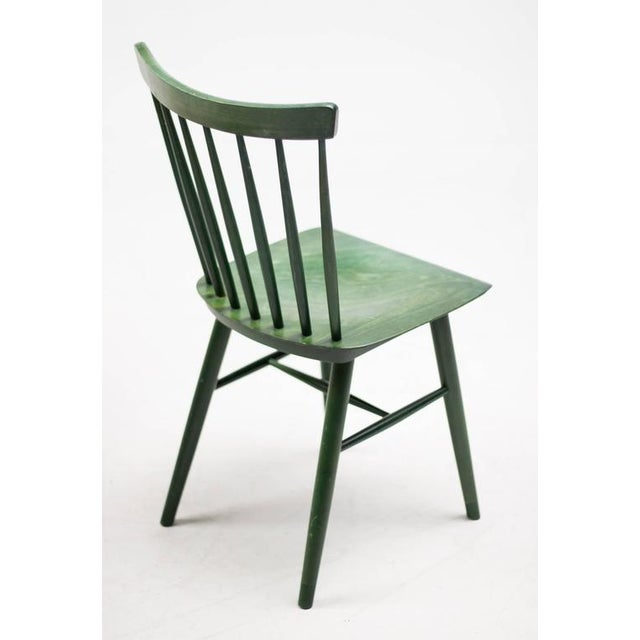 Dining set designed by Ilmari Tapiovaara in green dyed ash. Four spindle back chairs with bent plywood seat with matching...