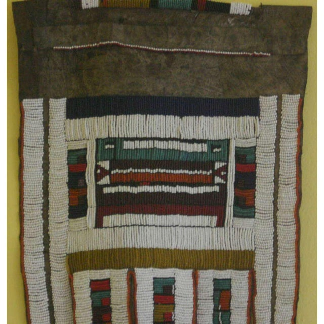 This is a vintage or antique African wedding apron made by the Ndebele tribe. It is a 5 fingered (goat?) leather backed...