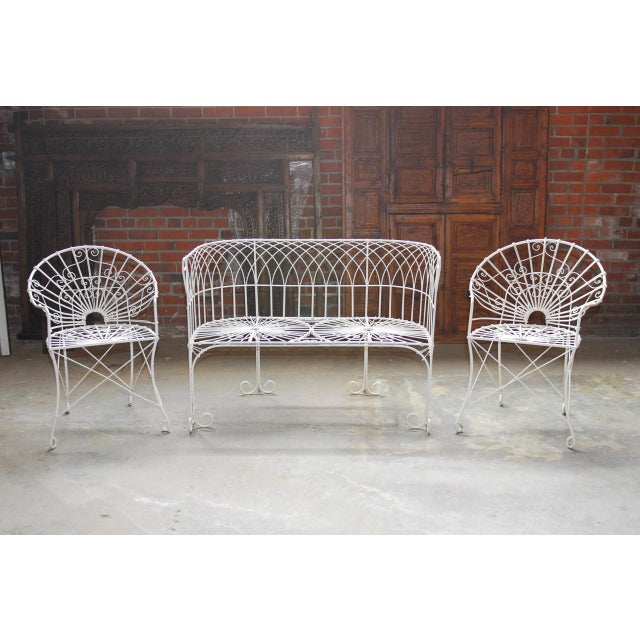 Fantastic set of French wrought iron and wire garden patio set consisting of two round back armchairs and one settee....