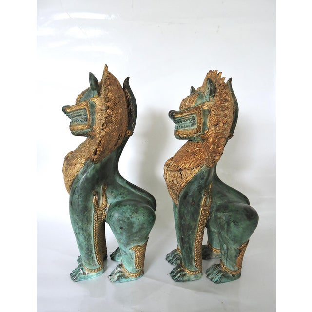 Thai temple Singha dragons or lions made of brass, or similar cast metal, highlighted with gilt/gold decorations - used...