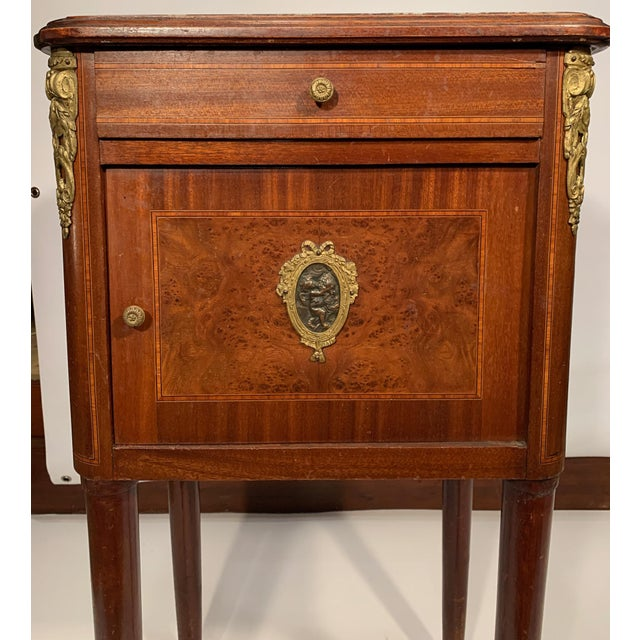 French bedside cabinet with one drawer, a marble top and ormolu decoration. The cabinet is lined with marble and features...