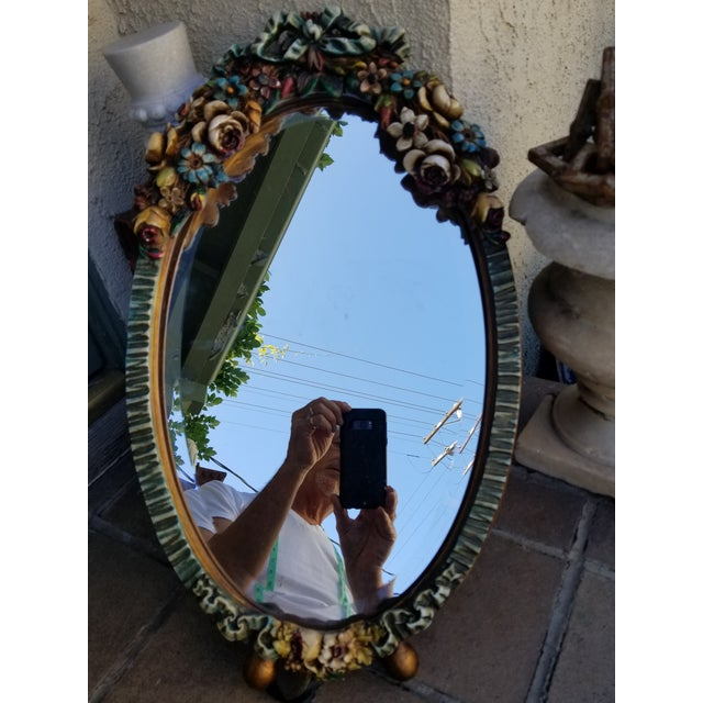 A huge Art deco barbola mirror encrusted with cabbage roses and floral garlands topped with a bow. England