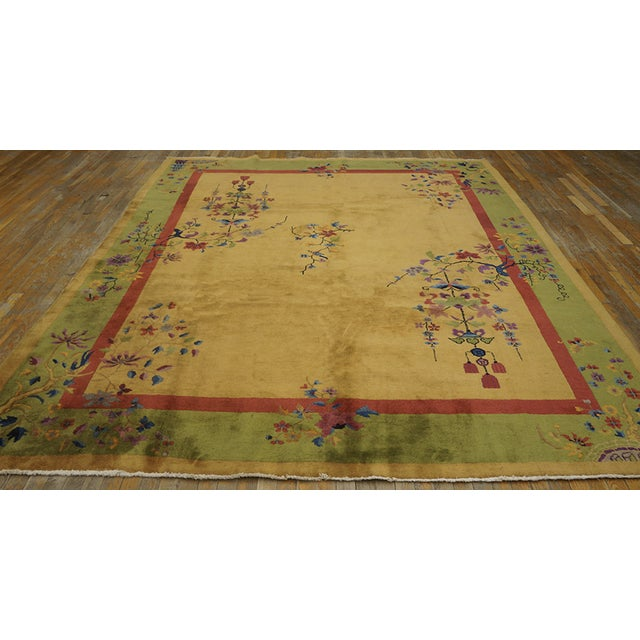 Antique Chinese Art-Deco Rug with a golden background surrounded by a crimson border and a floral design.