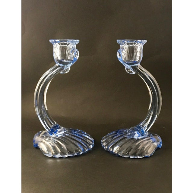 Offering a pair of Cambridge Caprice glass candlesticks in midnight blue. The candlesticks stand atop applied glass clam-...