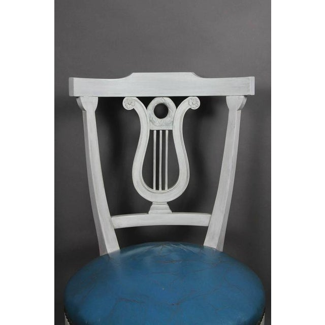 Curved rectangular crest rail over a lyre form splat, circular seat raised on shaped square tapered legs.