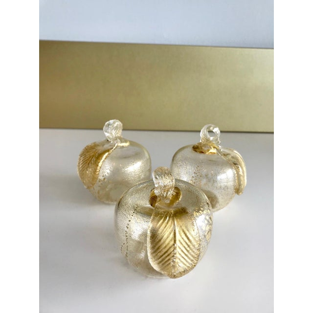 Set of three gorgeous handblown Murano glass figurines in the form of apples with 24K gold mica flecks. The apples feature...