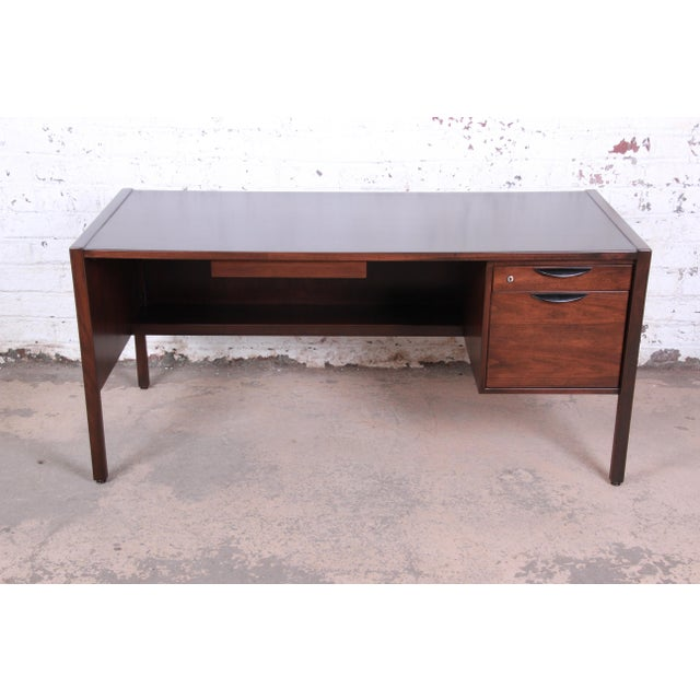 An exceptional mid-century modern walnut executive desk designed by Jens Risom. The desk features gorgeous walnut wood...