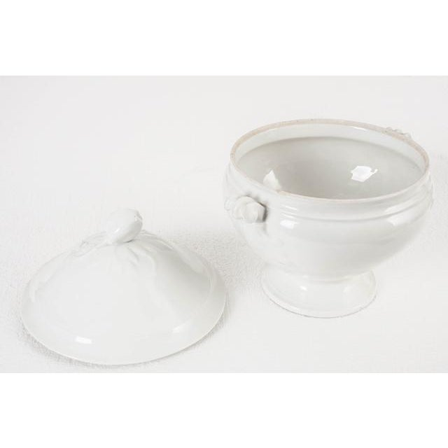 A beautiful glazed, white ironstone tureen with a pedestal base that is perfect for serving guests soups, stews, and...