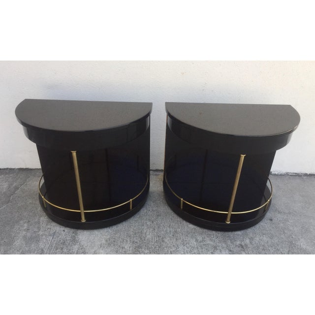 Elegant pair of black lacquered demi-lune side tables with brass details by Henredon. Lacquer finish shows wear including...