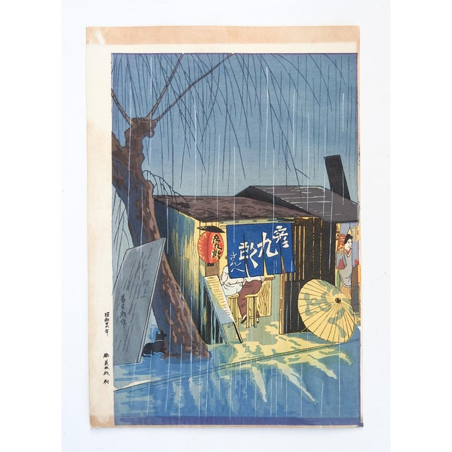 Woodblock print on paper by Tokuriki Tomikichiro. Noodle Restaurant on a Rainy Night, circa 1950's. Unframed, age toning...
