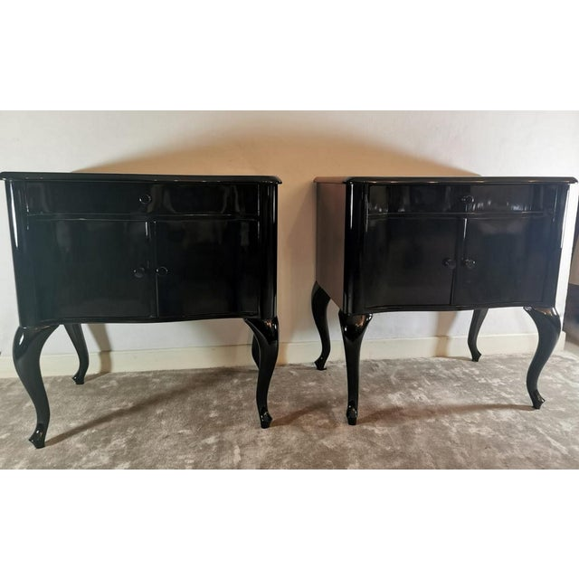 Pair of black mahogany nightstands lacquered and polished; the knobs of drawer and doors are matched; the two bedside...