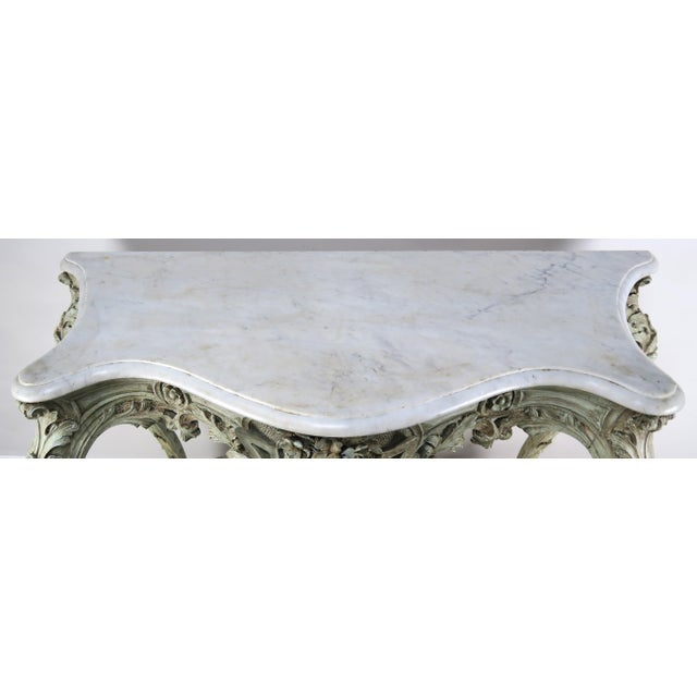 19th century French Rococo style painted console with Carrara marble top. The console is ornately carved with a center...