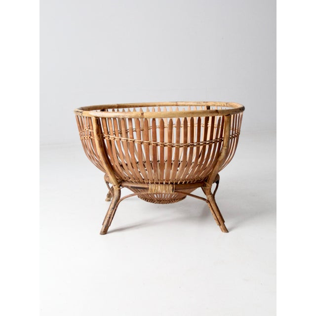 This is a large mid-century rattan basket on stand. The large round slat basket features a rattan frame with legs. Store...