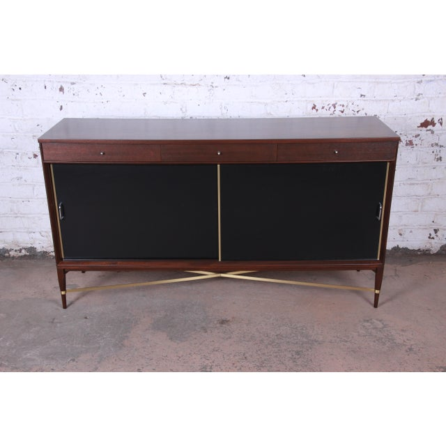An exceptional mid-century modern mahogany and brass sideboard credenza designed by Paul McCobb for his Calvin Group...
