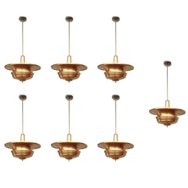 Art Deco era streamline copper ceiling hanging pendant with large copper saucer shade connected to a hanging stem....