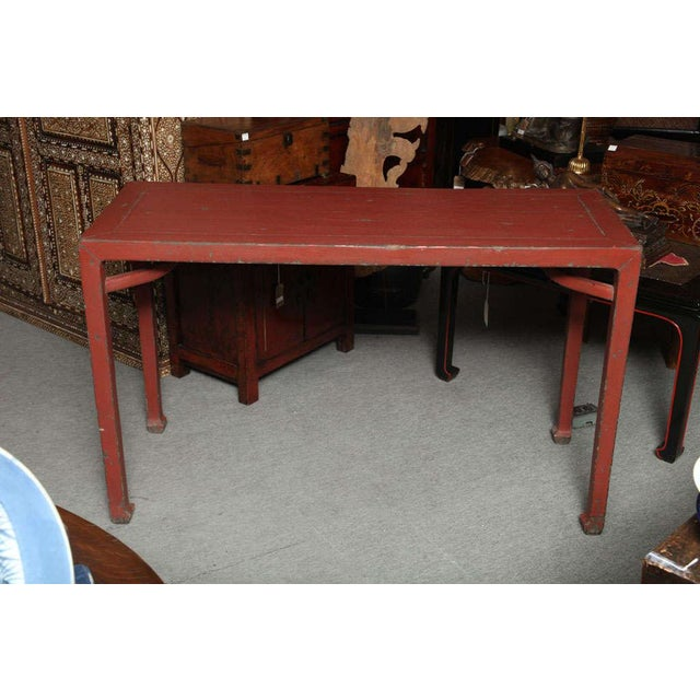 A 19th century Chinese red lacquered elmwood linen covered console table. This table adopts an unusual classic shape as...