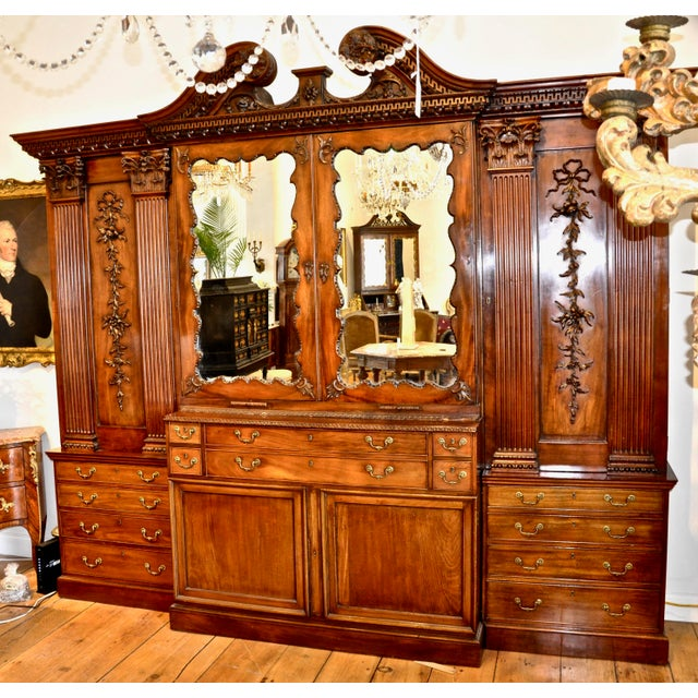 George III mahogany breakfront bookcase, 18th century The broken swan's-neck pediment with gadroon- and dentil-carved...