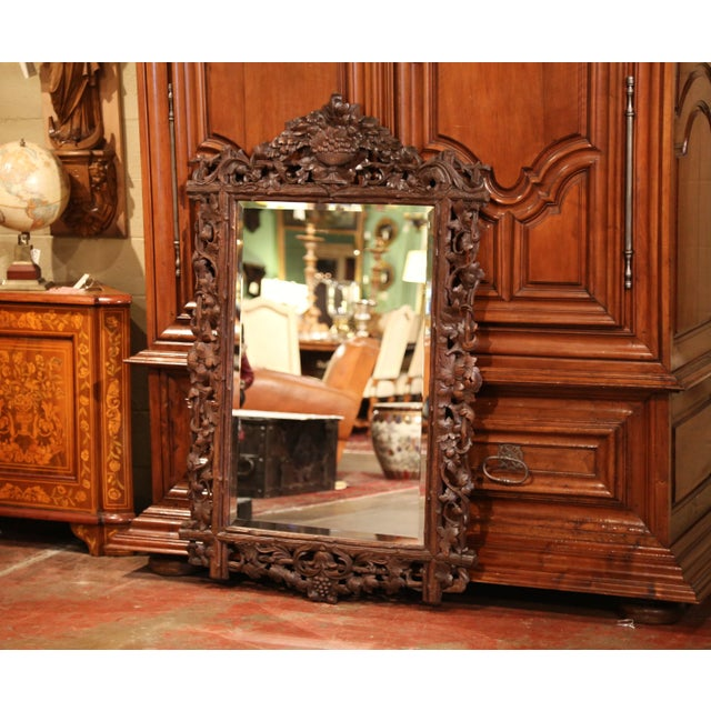 This large antique wall mirror was crafted in the Alps of France, circa 1870. The hand carved fruit wood mirror features a...