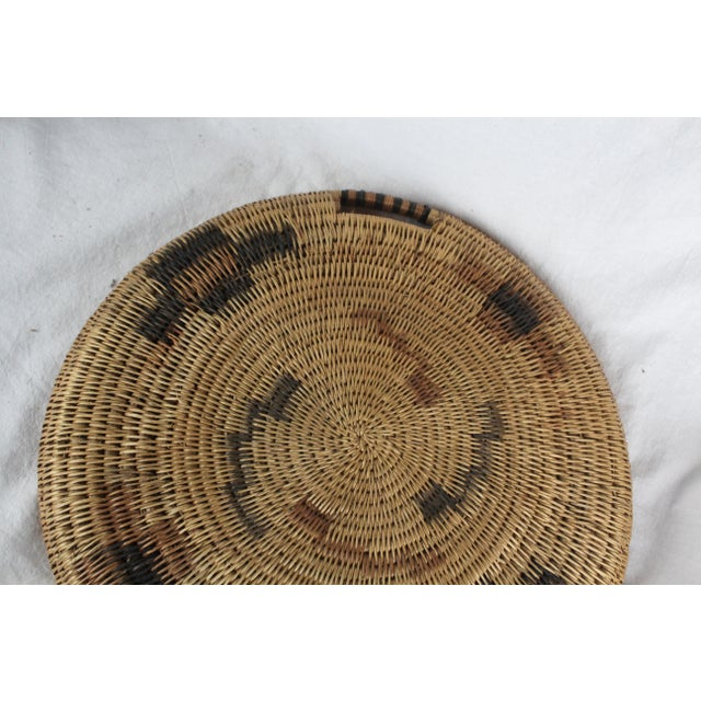 Handwoven textile Southwestern tribal platter in cross pattern with varying shades of brown and tan. Two handles.