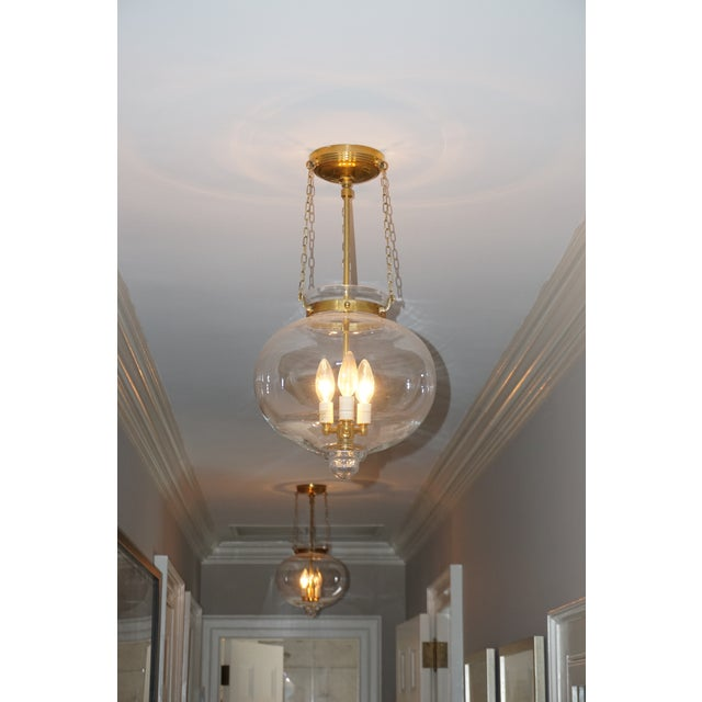 Designed by Chamleon Fine Lighting in New York City. hand blown murano glass, onion shaped cast with banded brass detailing.