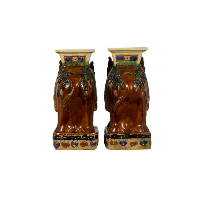 Pair of heavy, vintage elephant stands with colorful decorative detailing. One foot repaired.
