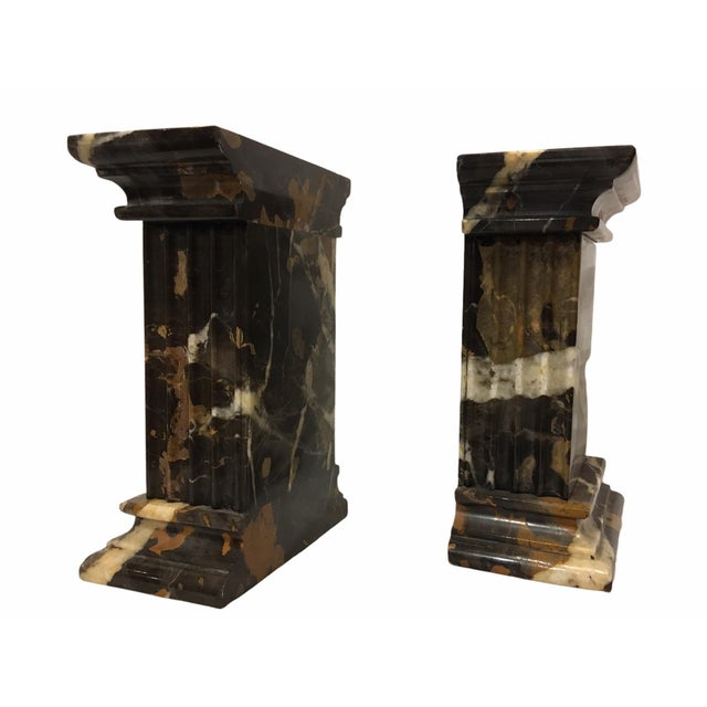 Handsome pair of vintage neoclassical marble bookends. Each piece is significant in weight and feature colors of black,...