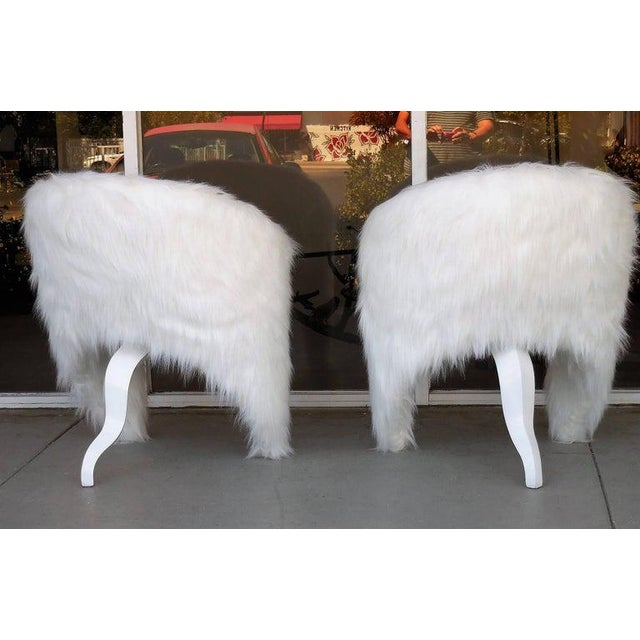 A pair of surreal lounge chairs. The back envelopes the seat and become the front legs. The shape is balanced by a wood...