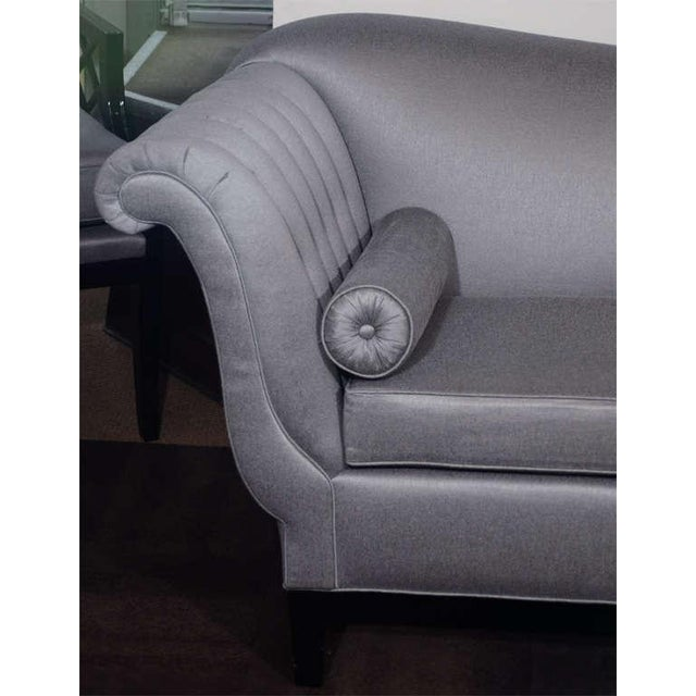 Highly stylized Hollywood sofa with sinuous back design and scrolled arms. Sofa has channel tufted arm design with button...