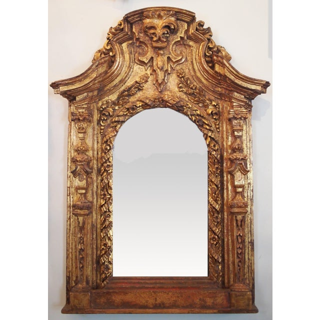 A 17th century Italian frame presented as a mirror, the frame arched and surrounded by a deeply carved garland intertwined...