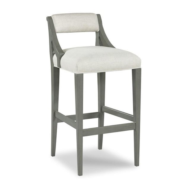 An upholstered back is situated above an upholstered seat with welt trim that is elevated over four squared tapering...