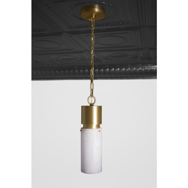 This contemporary light made of brushed brass and alabaster is part of the Orphan Work brand and can be used as a ceiling...