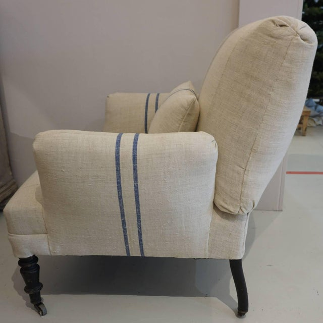 Napoleon III Fauteuil on rollers. Newly re upholstered in antique neutral French burlap back linen with dark blue centered...