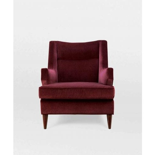 The Benjamin Club Chair by Studio Van den Akker features a solid wood frame with splayed legs that are available in a...