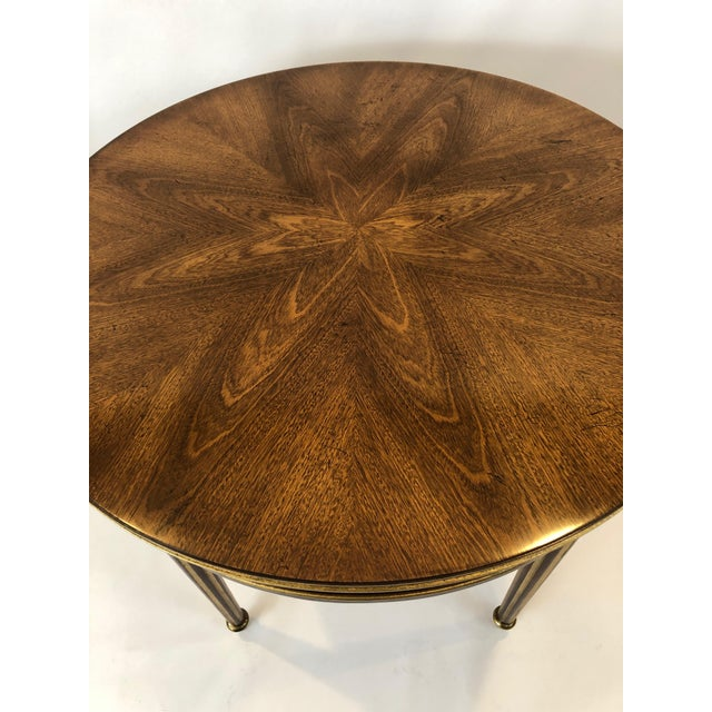 A sublime Regency style round side table having beautifully bookmatched wood on top that creates the shape of an ethereal...