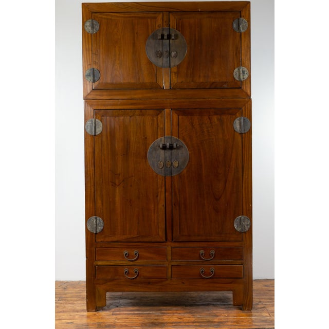 A Chinese vintage elmwood compound wedding wardrobe in two parts, with two sets of double doors, lower drawers and metal...