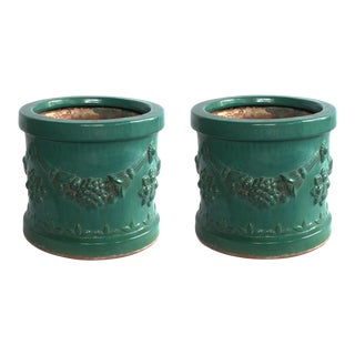 A robust pair of Malaysian teal-glazed terracotta planters with raised floral garland