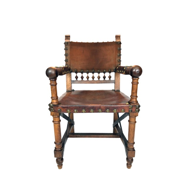 A Medieval Gothic style 19th Century Spanish Renaissance Revival Armchair. The chair is walnut with a original leather...