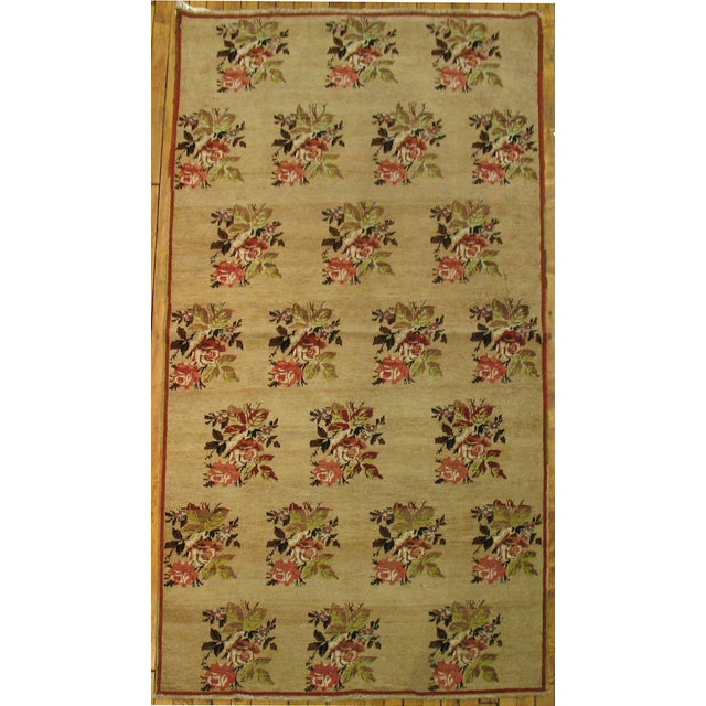 A Turkish rug features an all-over floral pattern. Lovely palette of greens and reds on a camel colored ground. Circa 1950.