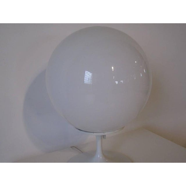 A white tulip table lamp with white round globe top manufactured by the Stemlite and Design Line Company.
