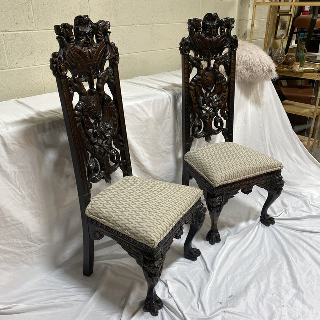 Very unusual carved wood chairs with north wind face and claw feet. Reupholstered in a nice off white upholstery weight...