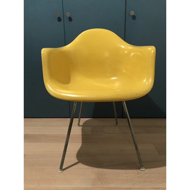 This is an early Eames fiberglass shell chair is in excellent condition with no chips or cracks. The color is a bright...