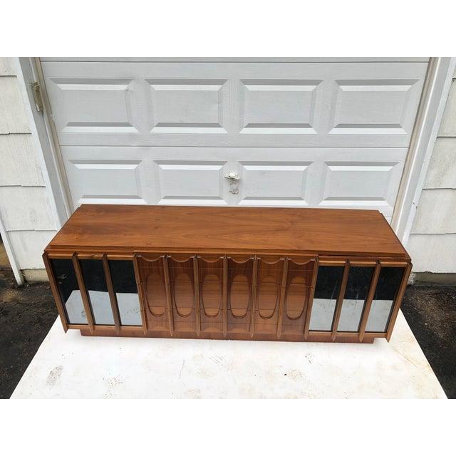 This striking brutalist modern nine drawer dresser features sculpted walnut finish with mirrored trim details. At 80...