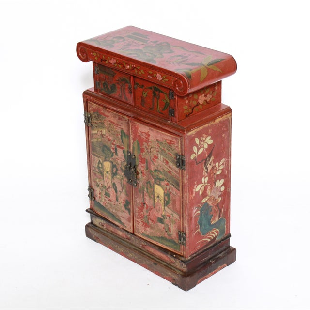 Chinoiserie red and figural painted diminutive cabinet with two small doors over two larger doors, interior drawer and one...