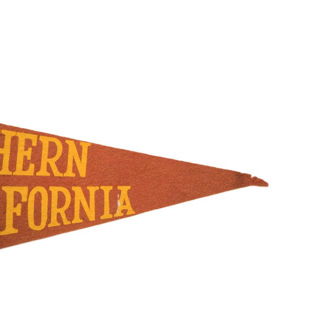 :: University of Southern California emblem featuring imagery of three torches and a rising sun encircled first by the...