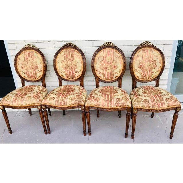 Stunning French Chairs nicely upholstered with a fancy material, beige & burgundy with brown accent flowers. The wood is...