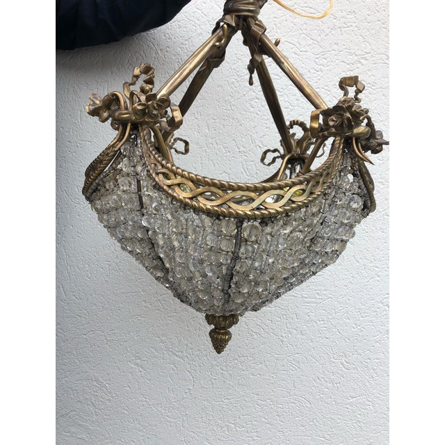 Striking and very unusual antique brass and beaded crystal chandelier adorned with brass ribbon swag and florettes with...