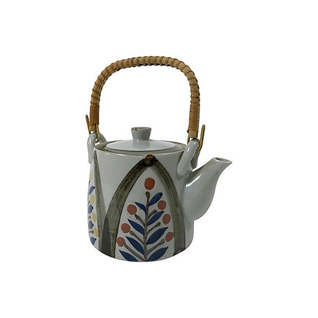Mid century modern Japanese ceramic teapot with a hand-painted floral design and woven rattan handle.